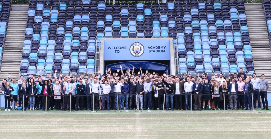 Smile! Manchester City staff celebrate the launch of the new crest inside the Academy Stadium